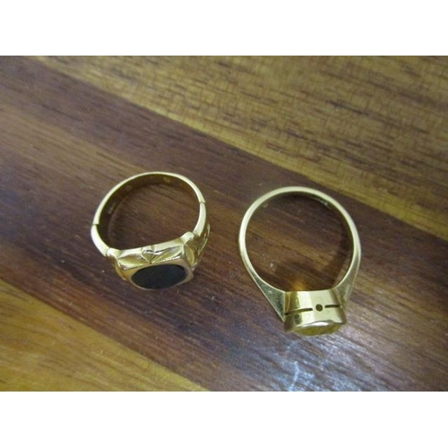 14 - An 18ct yellow gold and citrine ring and a yellow metal gold ring set with a black plaque stone, pos...