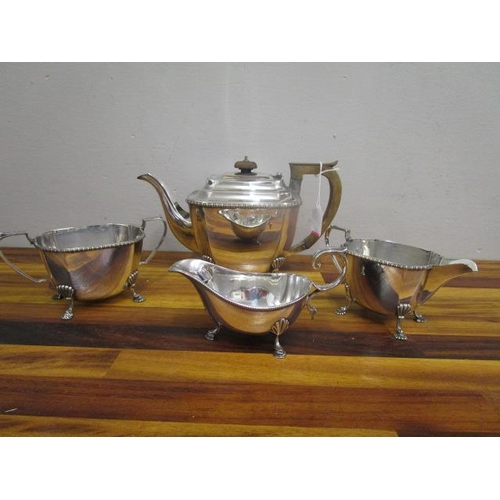 24 - A silver plated three piece tea set and a silver plated sauce boat...