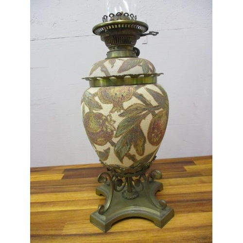40 - A late Victorian brass and ceramic oil lamp decorated with poppies and leaves...