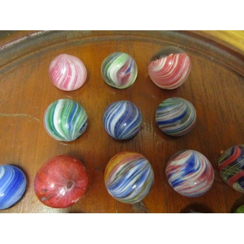 31 - A Victorian Solitaire game with thirty two Victorian glass marbles and one later marble with silver ...