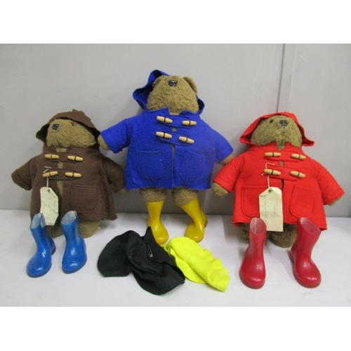 38 - A group of three Paddington teddy bears, two with hand written luggage labels attached to the coats,...
