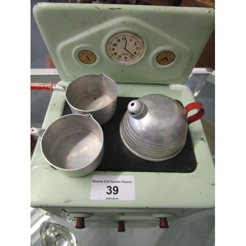 39 - An Amersham painted tin plate child's cooker with two pans and a kettle, circa 1950...