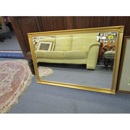 110 - A gilt framed contemporary wall mirror with bevelled glass plate and a framed and glazed print by Mo...
