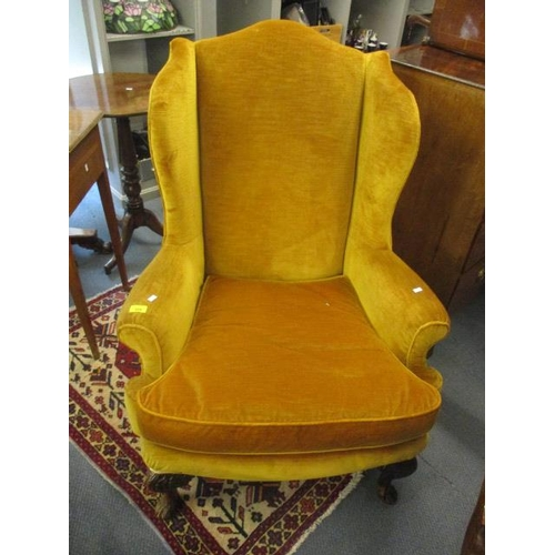 126 - A George III wing backed armchair in a mustard yellow velour upholstery with carved front cabriole l...