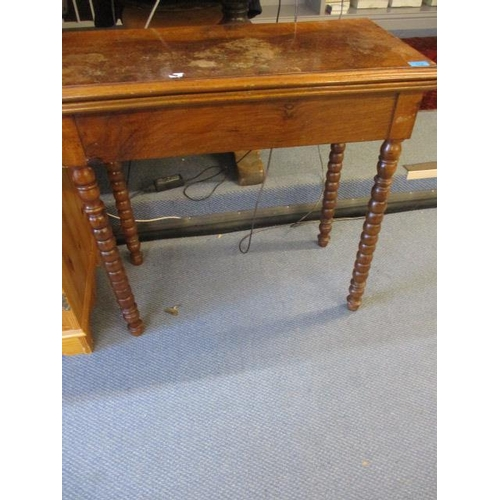 113 - A 19th century walnut card table with a rotating, fold over top on bobbin turned legs...