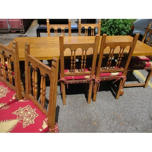 117 - An oak dining table with scrolled supports with six matching Medieval style dining chairs and two ca...