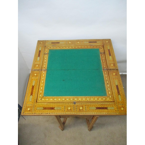 140 - An early 20th century bone/ivory and mixed veneered marquetry games table, with a rotating foldover ...