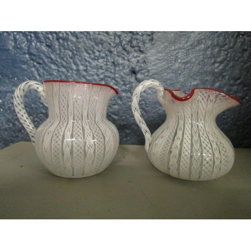 14 - Two French white latticinio glass cream jugs with red glass top rims, probably St Louis or Clichy, t...