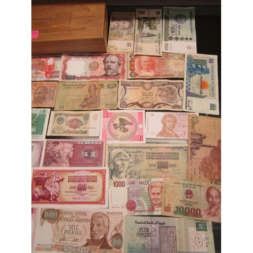 26 - A quantity of various banknotes from around the world in a Fortnum & Mason fruit confits box...