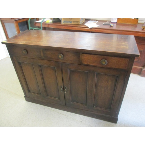 14 - An early 20th century oak sideboard having three inset drawers and twin cupboards below 39