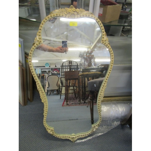 15 - An Ansonia white painted framed wall mirror with gilt highlights and flower head decoration, label v...