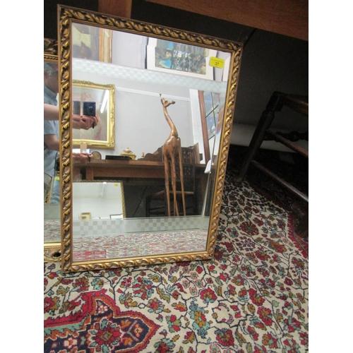 37 - A rectangular gilt framed wall mirror with leaf decorated gilt frame...