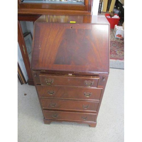 9 - A reproduction mahogany ladies bureau having fall flap above four drawers...