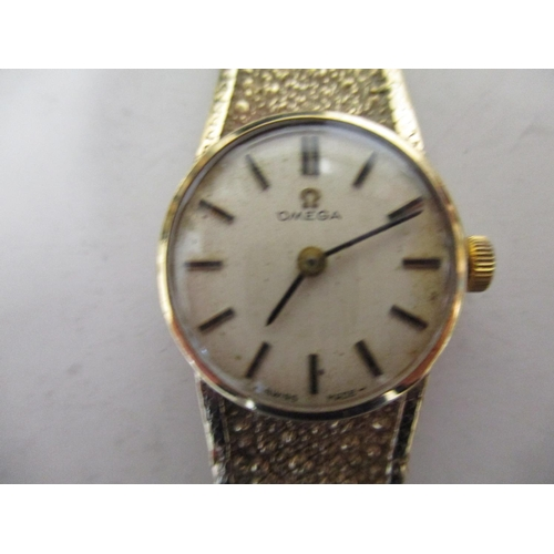37 - A ladies Omega 9ct gold bracelet wristwatch with champagne dial and baton hour markers, the case ser...