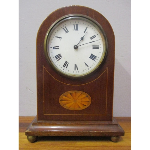 51 - An Edwardian mahogany 8 day, arched topped mantle clock having a white enamel dial with Roman numera...