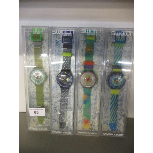 65 - Four cased Swatch watches to include three Scuba 200 and one other...