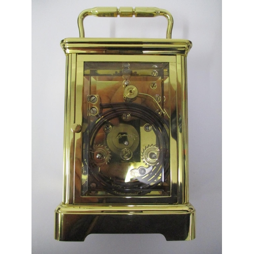 69 - A modern brass carriage clock with an eight day movement, striking on a gong, having a white enamel ...