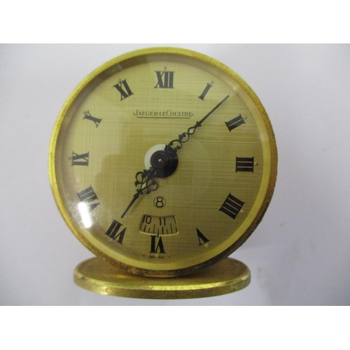 75 - A Jaeger Le Coultre miniature eight day travel alarm clock, having a 45mm gilt case, gilt dial with ...