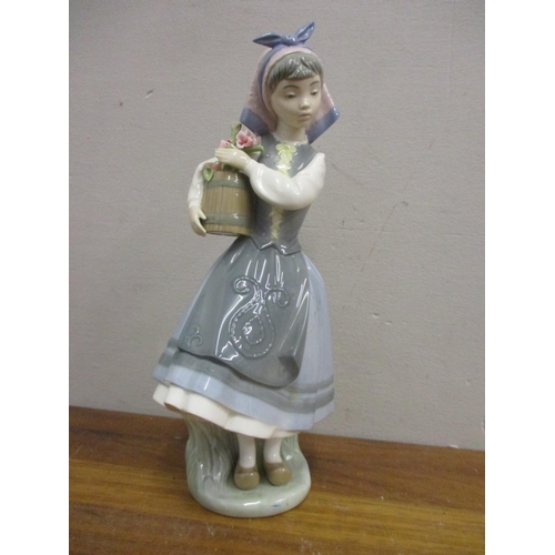 34 - A Lladro figure of a continental girl holding a barrel of flowers...