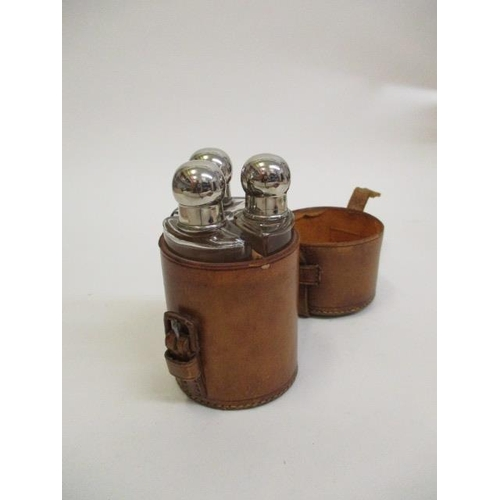 7 - A leather cased set of three glass bottles with stoppers and caps, 5