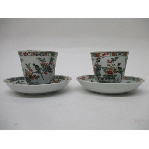 29 - A pair of early 18th century famille vert cups and saucers with a bell shaped cup, on a foot rim and...