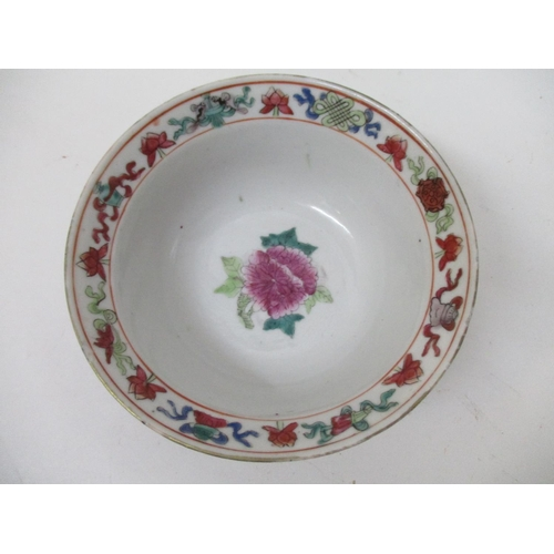 40 - A 19th century famille rose bowl with a flared lip decorated with a peony and leaves and a band of o...