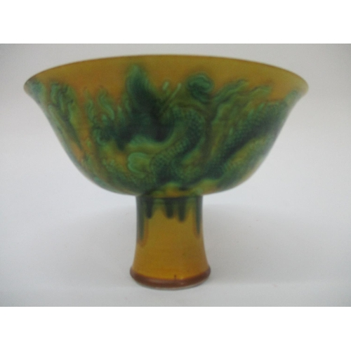 1 - A 20th century Chinese stemcup with a streaky green glaze on a mustard coloured ground, incised with...