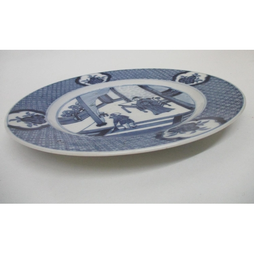 20 - A Kangxi Chinese blue and white plate decorated with a man and a child on a veranda, within a patter...
