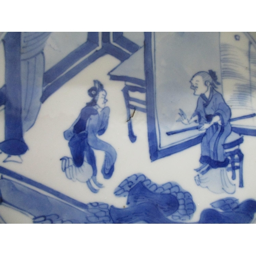 21 - A Kangxi Chinese blue and white plate decorated with two figures on a veranda, within a patterned bo...