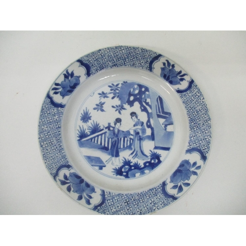 23 - A Kangxi mark and period Chinese blue and white plate, decorated with two women in a garden setting,...