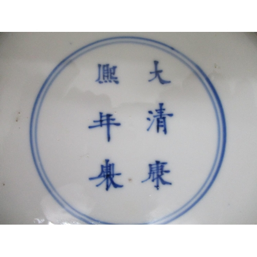 24 - A Kangxi mark and period Chinese blue and white plate, decorated with four men, one sat on a stool, ...