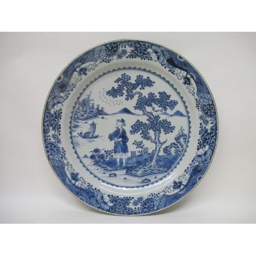 28 - A late 18th century Chinese blue and white charger decorated with a man standing by a tree, with a r...