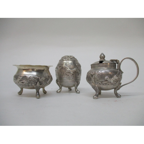 6 - An Indian silver three piece condiment set of bulbous form, with embossed and chased ornament...