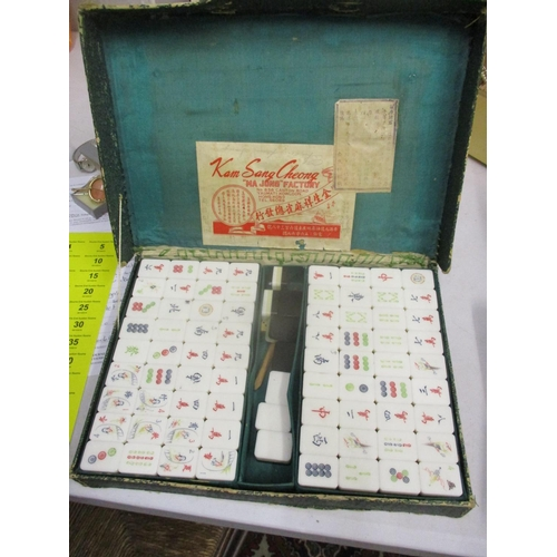1 - A 20th century Mah Jong set with plastic counters, in a green card case...