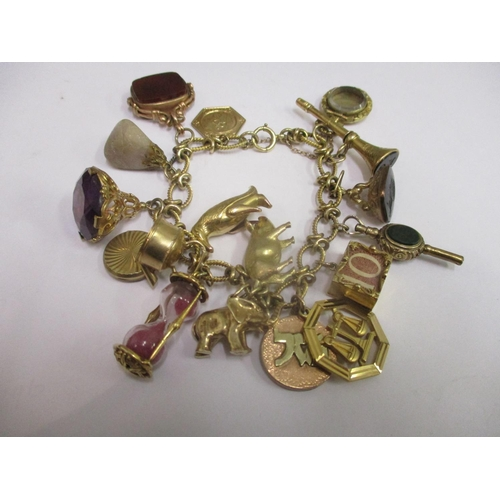 1 - A 9ct gold charm bracelet with an assortment of charms attached, total weight 78.30g...
