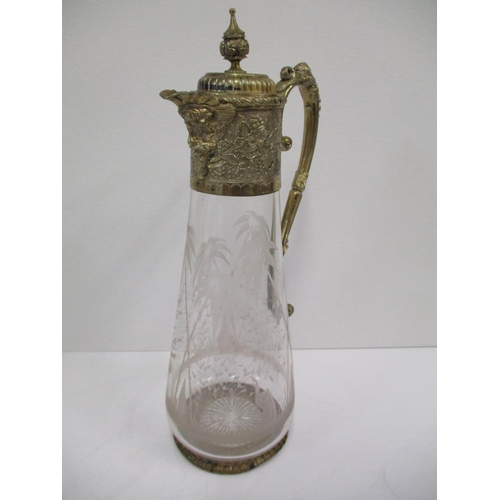 29 - An Edwardian gilt metal and glass claret jug with grape and leaf design, the engraved glass body cut...
