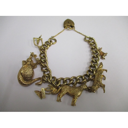 3 - A 9ct gold charm bracelet with an assortment of 9ct gold charms attached, 79.60g...