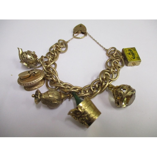 4 - A 9ct gold charm bracelet with an assortment of 9ct gold charms attached, total weight 86.55g...