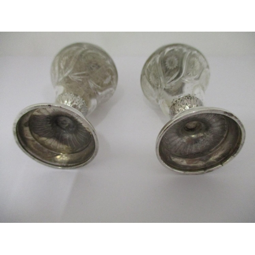40 - A pair of American silver and clear glass peppers, stamped sterling with detachable, pierced lids an...