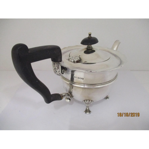 46 - A silver teapot by Henry Wilkinson Sheffield 1928, on four scrolled feet, having ebony handle and fi...