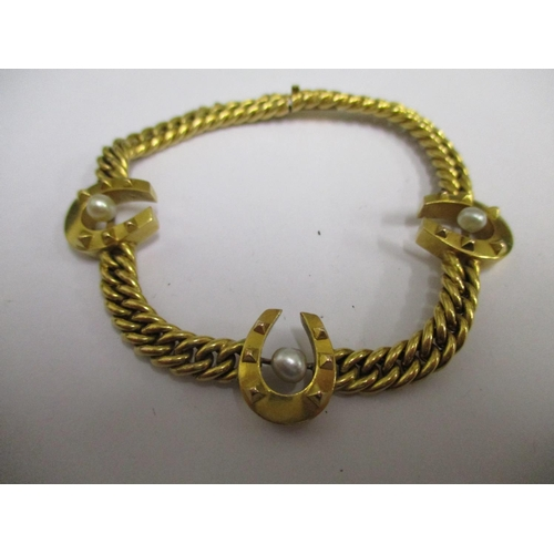 7 - A gold coloured bracelet, set with three horseshoes and cultured pearls complete with original box, ...