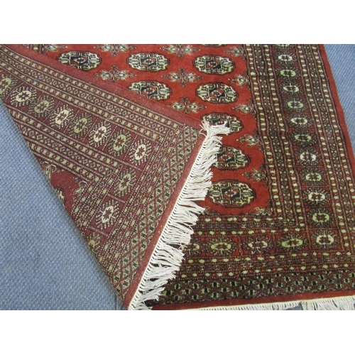 458 - A Middle Eastern red ground rug having geometric designs and tasselled ends, 82
