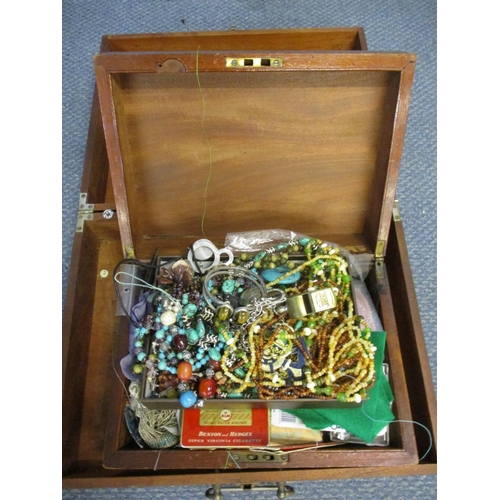502 - A Victorian mahogany box and contents to include costume jewellery and a Thunderball whistle and a s...