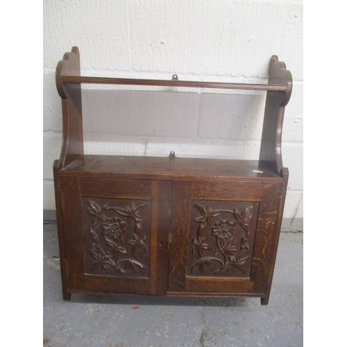 40 - A late 19th/early 20th century oak wall hanging cabinet having two shelves above two carved doors, 3...