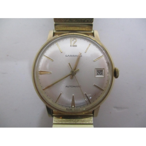 23 - A Garrard gents gold coloured automatic wristwatch. The silver dial having baton markers, centre sec...