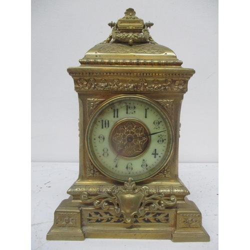 45 - A late 19th century French ornate brass mantle/timepiece clock having twin carrying handles above em...