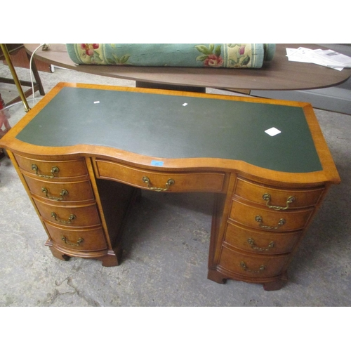 26 - A reproduction walnut serpentine fronted twin pedestal desk having a green leather topped scriber an...