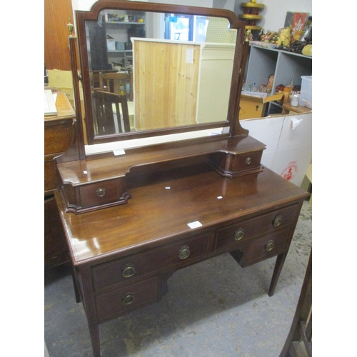 32 - An Edwardian mahogany dressing table having a swing mirror above drawers and tapering legs 60 1/2