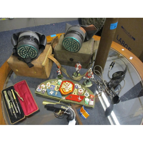 38 - Military related items to include two gas masks, modern painted lead figures of soldiers, and a quan...