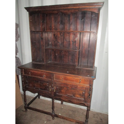 7 - An early 20th century oak dresser having a plate rack above drawers and cupboards 74 3/4
